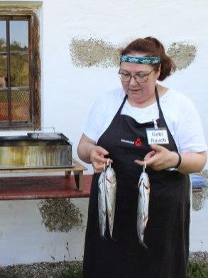 Da steigt die Vorfreude: Gabi Rauch erklärt, wie man mit einem Angler-Expressgerät Forellen, Karpfen und Lachs räuchert. © Bezirk Oberbayern, Archiv BHM, Aufnahme: Rosi Raab.