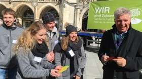 Die jungen Teilnehmerinnen und Teilnehmer des 125. Herrschinger Grundkurses begrüßen Münchnes Oberbürgermeister Dieter Reiter bei ihrer Aktion auf dem Marienplatz – und lassen ihn ein Blatt für den Wunschbaum beschreiben. (Foto: Bayerischer Bauernverband)