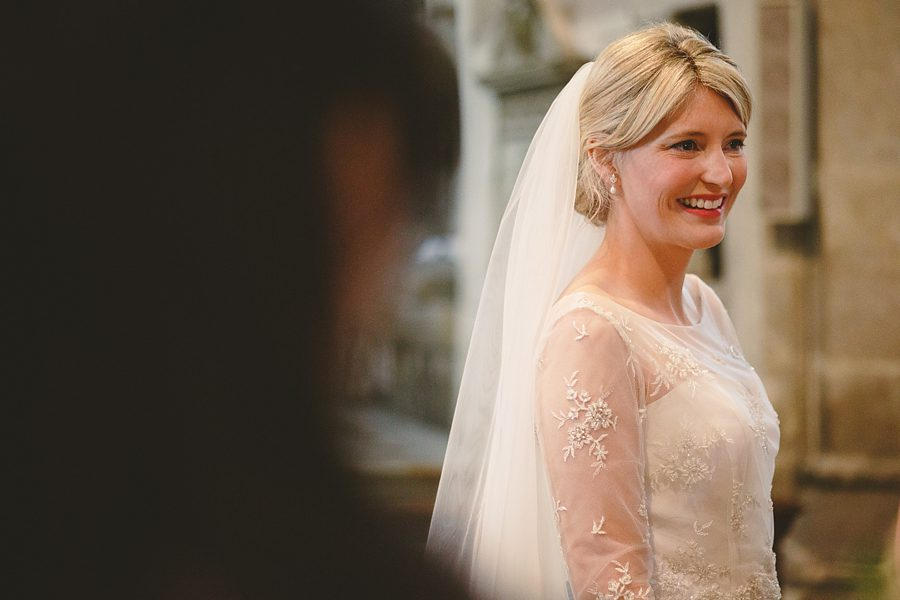 bride smiling at cirencester church by sam gibson