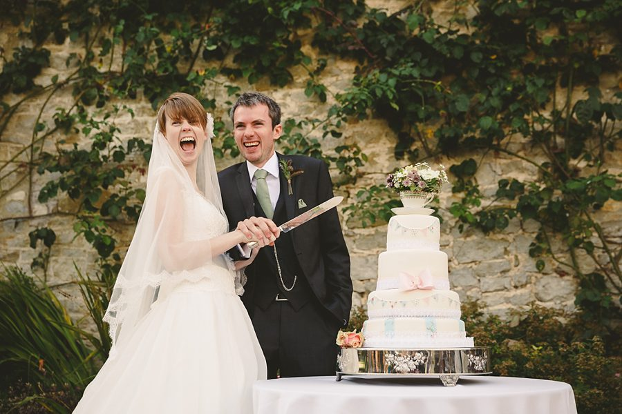 bride and groom cutting their cake at priston mill by sam gibson