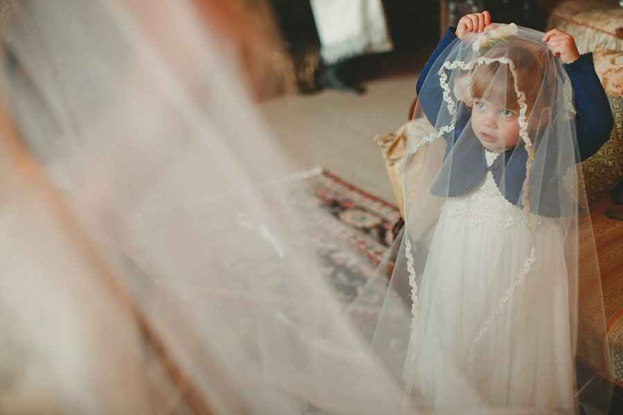 girl playing with wedding dress veil