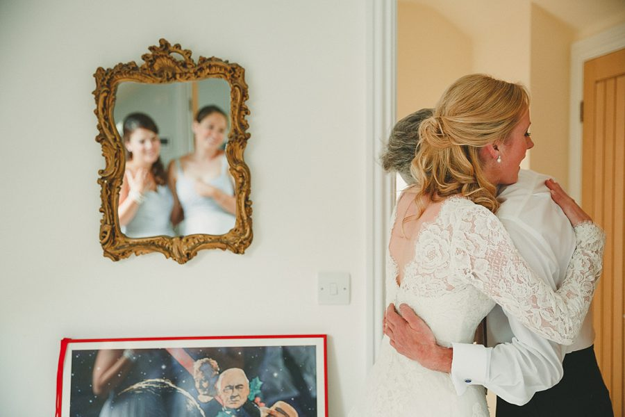 bride hugging father in her wedding dress at home