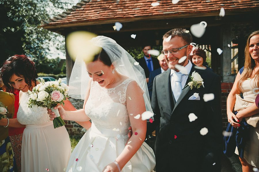 bride and groom leave to confetti after church wedding
