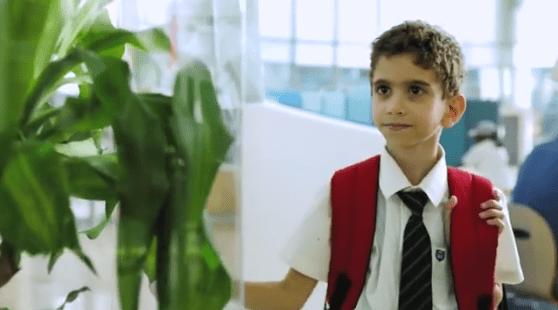 school kid looking at plant