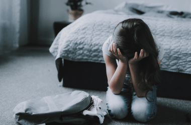 Sad child on bedroom floor with backpack
