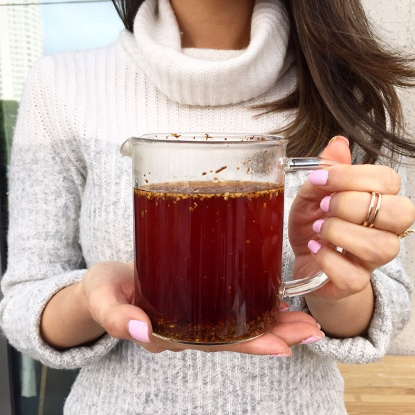 A woman looks on as tea infuses with water in vivid brewpot