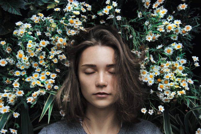 ঘুম না হলে যেসব সমস্যা হতে পারে woman closing her eyes on white flower
