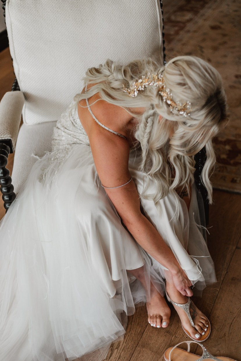 Bride getting ready with jewelry and gown.
