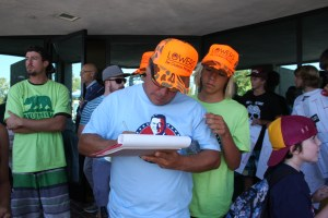 Michael Takayama of San Clemente adds his name to a list of those opposed to the toll road as his son Kaimana looks on. Photo by Andrea Swayne