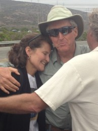 Laurie Headrick of San Clemente embraces Steve Nehterby and her husband Gary Headrick in celebration of the closure of San Onofre Nuclear Generating Station. Photo by Jim Shilander