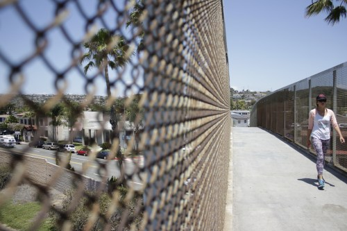 Sara Medlin walks across the pedestrian bridge Tuesday in the South El Camino Real neighborhood. A group of students from Cal-Poly San Luis Obispo is looking to perform an economic and development study on the area as part of a class project.  Photo: Eric Heinz