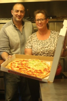 Sam Cimino, owner, and Lara Hadjokas, manager, of Mama Cimino's Surfside Pizza in San Clemente pose with one of their 20-inch pizzas. Photo: Eric Heinz