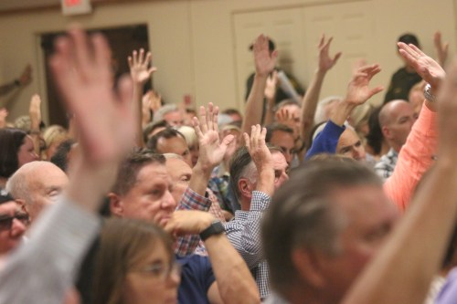 People raise their hands after being asked if they were there because they have been affected by or had concerns about sober living homes. Photo: Eric Heinz