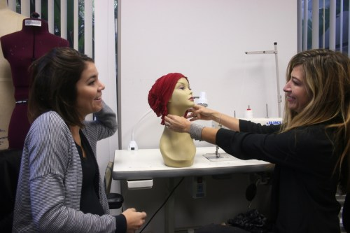 Natalie Foley, left, the Chemo Beanies product developer, and owner and founder Adrienne Metz, examine one of their products on a mannequin. Photo: Eric Heinz