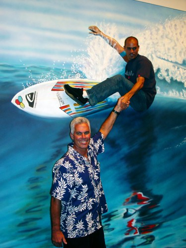 In a photo taken backstage in 2003, pro surfer Kelly Slater shakes hands with artist Gary Prettyman while perched above him in a living picture of Prettyman's 1991 painting of Slater, titled 'Cutting Glass.' Photo: Courtesy of Laguna Beach Festival of Arts