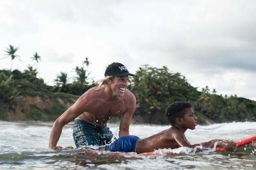 Dane Gudauskas, a San Clemente resident and part of the Positive Vibe Warrior organization, pushes a child into the surf at a break in Trinidad and Tobago. Photo: Courtesy of Jimmy Wilson/Vans