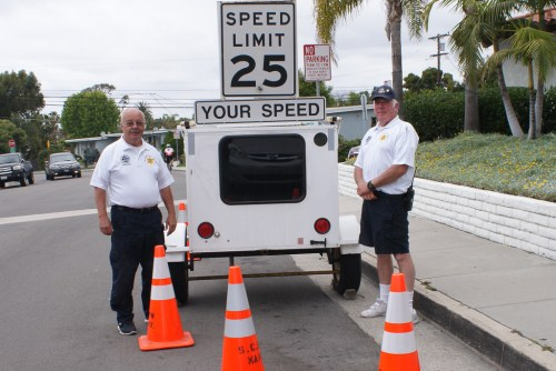 Two RSVP volunteers stand near a speed gauge. Photo: Courtesy of Lou Leto