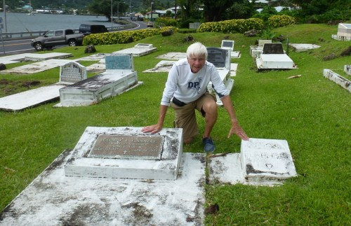 Tom Blake touches the two gravestones of an American's parents in Pago Pago, American Samoa