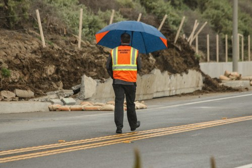 City officials survey the damage of a landslide that broke through a cement barrier on Wednesday, Feb. 13, along N. El Camino Real at the 203 marker. The city expects the road to be closed through tomorrow. Photo: Eric Heinz
