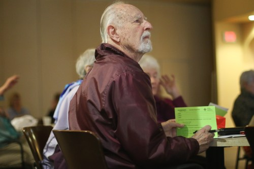 "Keith Leaburn, 86, listens to the presentation ""Medical Cannabis: Promoting Health without Creating Potheads"" while holding an information card on Feb. 28 at the Dorothy Visser Senior Center in San Clemente. Photo: Eric Heinz"