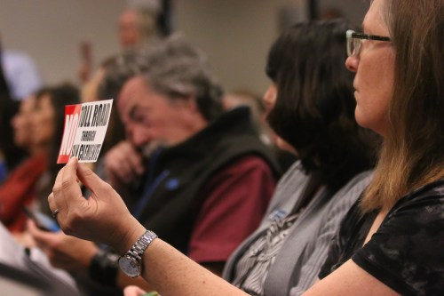 "A woman holds a ""No Toll Road Through San Clemente"" bumper sticker at the April 11 Transportation Corridor Agencies joint board meeting in Irvine. Photo: Eric Heinz"
