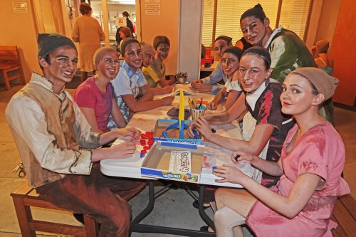 Backstage at the Pageant of the Masters, cast members socialize and play games while waiting to appear on stage as living paintings. That's San Clemente's Jackson Brownell, 13, seated in the rear, left side of table. Photo: Fred Swegles
