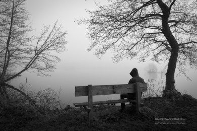 Melancholy emotions concept: depressed man sitting on a bench at a lake.