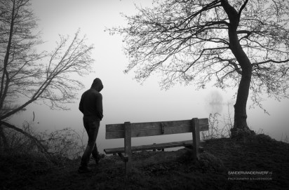 Depressed man aproaching a bench at a lake on a foggy day.