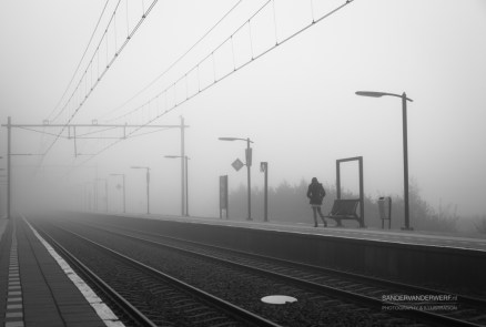 Woman alone at a train station, waiting for the train on a foggy day in autumn.