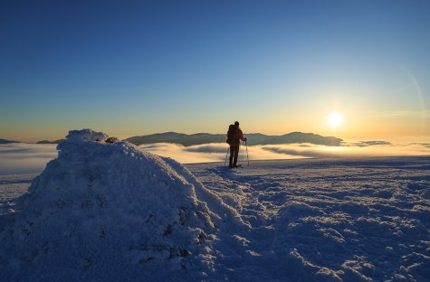 Hiker in the snowcovered Vercors during a colorful, winter sunset.