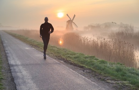 Running in the foggy, Dutch countryside near a windmill during a tranquil sunrise.