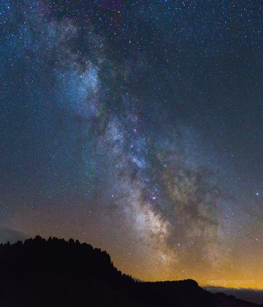 Night sky with Milky Way and Galaxy above the horizon.