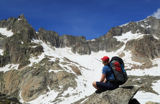 Female hiker enjoying the view of the mountains during a summer trekking vacation.