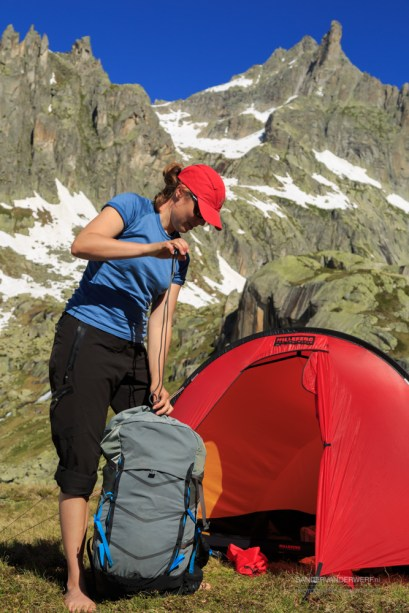 Hiker woman packing her backpack in front of a red tent in the Swiss mountains.
