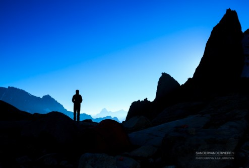 Silhouette of a person looking at the mountains just before sunrise.