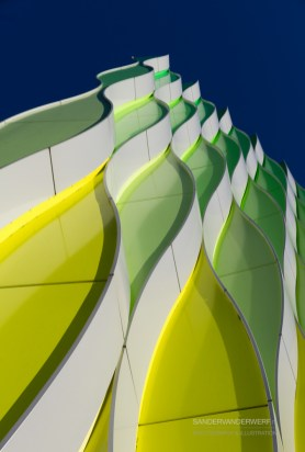 Curved elements in silver, green and yellow.