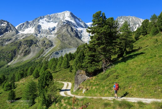 Hiker walking on a gravel road in the beautiful mountains of Arolla.
