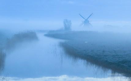 foggy dawn at a windmill in the Dutch countryside.