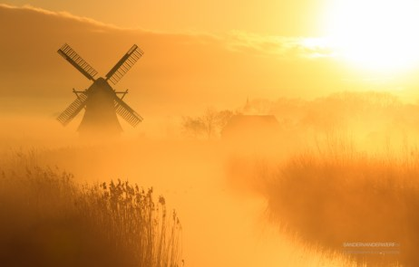 Windmill during a foggy sunrise in the Dutch countryside.