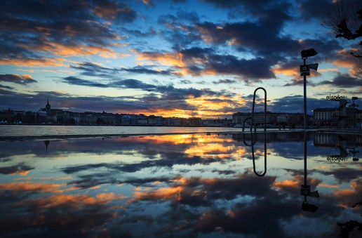 Winter sunset reflected in a pubble on pier Bains des Paquis in Geneva.