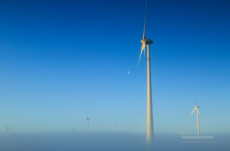 Wind turbines generating sustainable energy on a foggy morning in the Dutch countryside.
