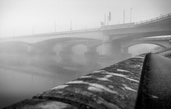 Footpath under two old bridges on a foggy, autumn morning. Lyon, France.