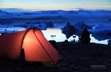 Female hiker cooking beside a tent at the shore of Jokulsarlon.