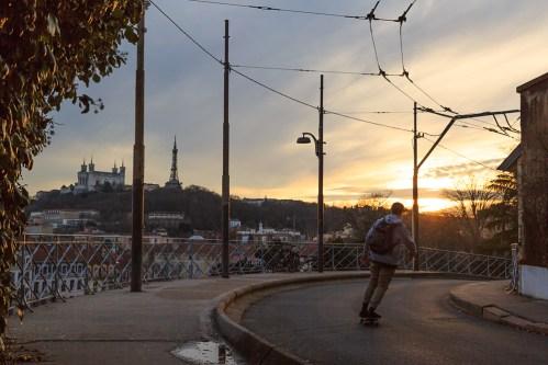 Skateboarding toward the sunset.