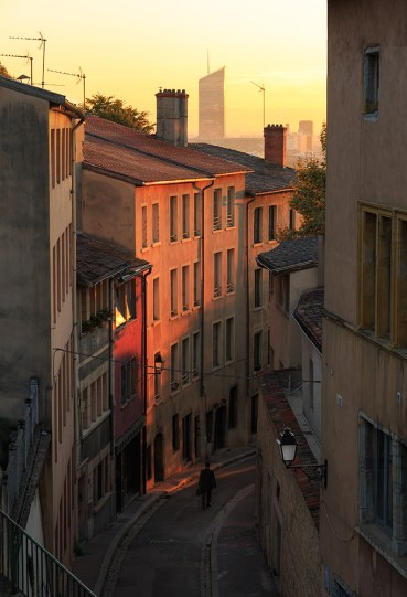 A man walking in a charming alley in Vieux Lyon, the old town of Lyon, during sunrise.