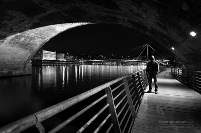 Man with hoody standing in a tunnel under a bridge at night.