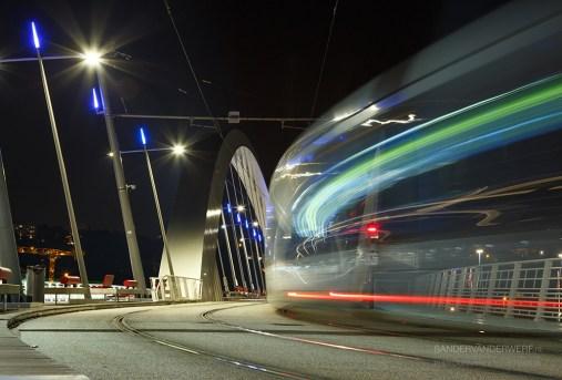 Tram speeding over a bridge at night