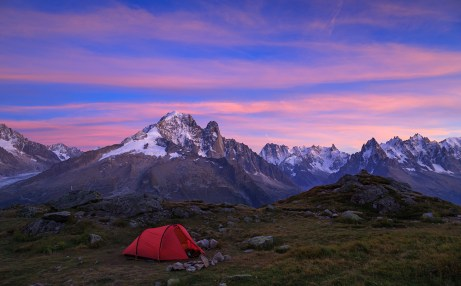 Red tent in the mountains near Chamonix during a colorful sunset.