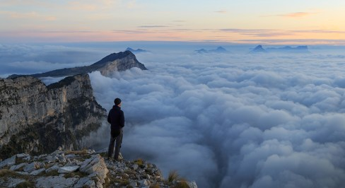 Hiker looking over a sea of clouds in the mountains at dawn. Vercors, France.