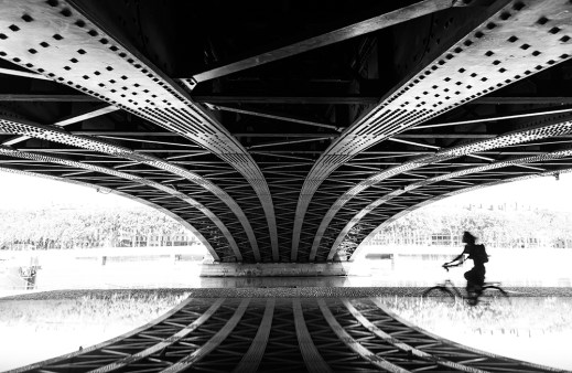Silhouette of a woman cycling along the Rhone river in Lyon on a summers day.